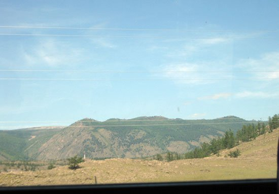 Вид из окна автобуса по дороге на Ольхон озера Байкал: вдалеке горы покрытые лесом. По дороге на Ольхон озера Байкал фотографировал мелькавшие за окном пейзажи.
