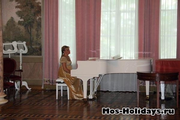 Девушка за пианино в колонном зале усадьбы Люблино